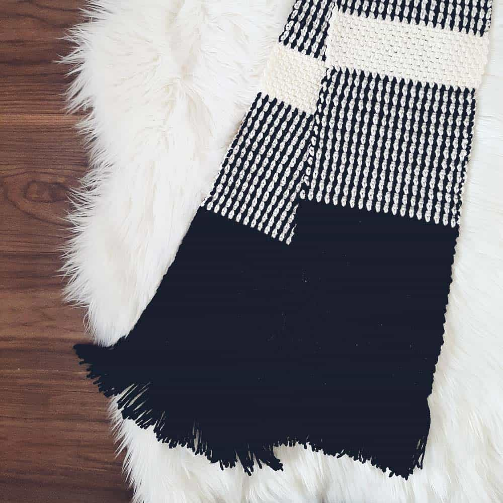 Crochet scarf, black and white, on rug
